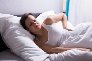 Woman resting in bed, suffering from back pain