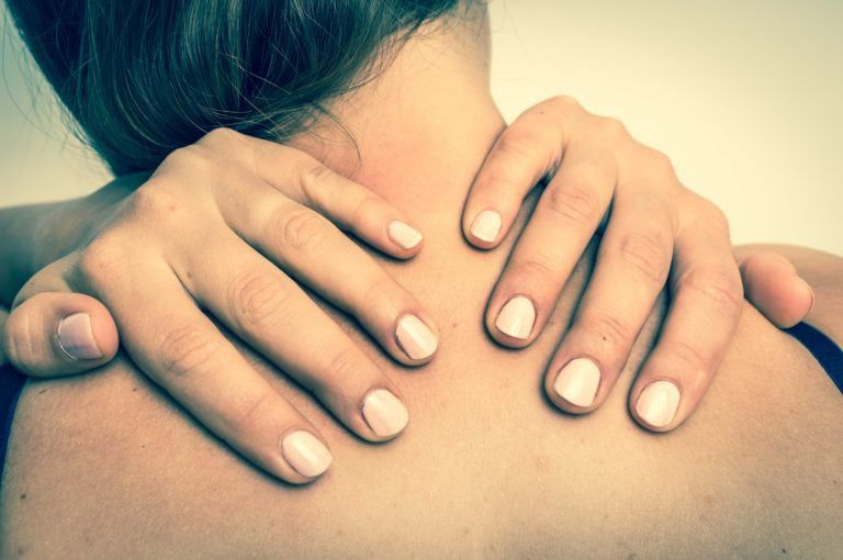 Woman reaching back and using her hands to massage her upper shoulders