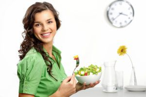 Woman dressed in green eating a salad and smiling