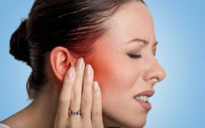 Woman touching face and grimacing from pain
